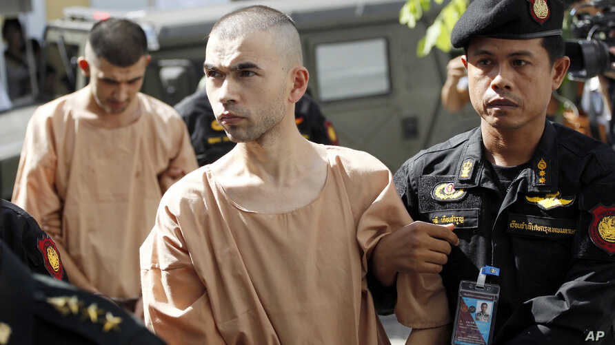 FILE - Police officers escort suspects in the blast at Erawan Shrine, Bilal Mohammad, front, and Mieraili Yusufu, rear, as they arrive at a military court in Bangkok, Thailand, Nov. 24, 2015.