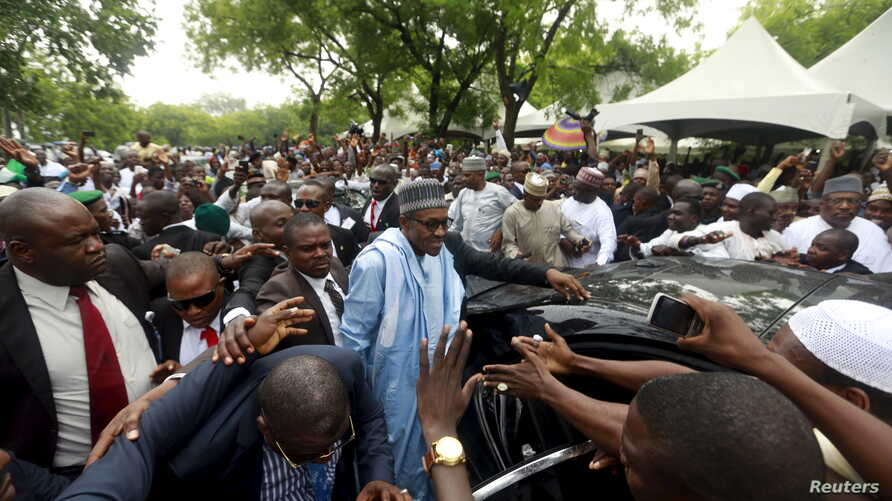 Nigeria's President Muhammadu Buhari (C) is shielded by security after prayers at the Abuja praying ground on the first day of the Muslim holiday of Eid-al-Fitr, marking the end of the holy month of Ramadan in Abuja, Nigeria's capital, July 17, 2015.