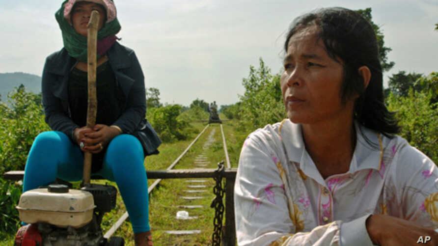 """Riding the rails in western Cambodia: The driver of a """"flying carpet"""" and her passenger head west towards the town of Pursat in central Cambodia along the buckled line in late October, closely followed by another flying carpet. This line will be upgr"""