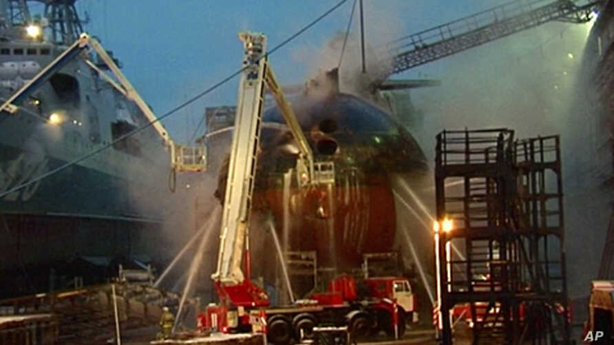 In this video image from Ru-RTR Russian state television channel, firefighters spray water on the Yekaterinburg nuclear submarine in a dock at the Roslyakovo shipyard in the Murmansk region, Russia. A fire that erupted while the Yekaterinburg was in