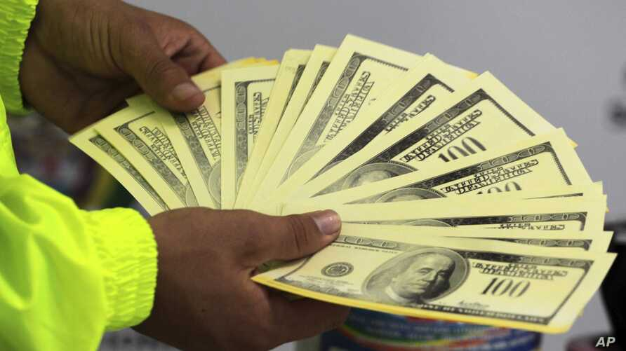 A police officer shows seized counterfeit dollars to the press in Cali, Colombia, Oct. 9, 2012.