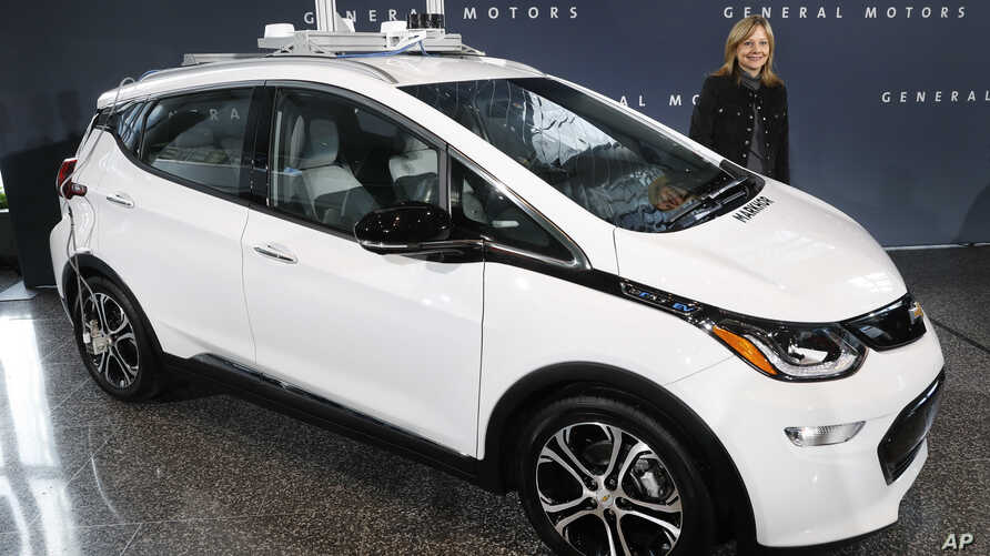 FILE - General Motors Chairman and Chief Executive Officer Mary Barra stands next to an autonomous Chevrolet Bolt electric car, Dec. 15, 2016, in Detroit.