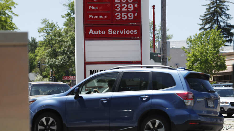 FILE - Prices for the three grades of gasoline light up the pump at a Conoco stationin east Denver, May 25, 2018.