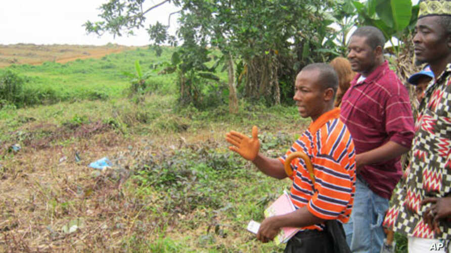 Community leaders in Nimba Point in Grand Cape Mount, Liberia, take Alfred Brownell (center) of Green Advocates, a member of the Rights and Resources Initiative, on a tour of land that had been cleared by Sime Darby, a Malaysia-based company.