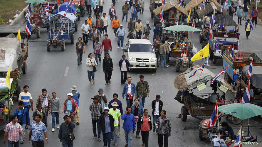 Rice farmers walk between their tractors on a main highway where they spent a night in Ayutthaya. Thai farmers called off a tractor drive to Bangkok's main airport to protest against not being paid under a rice subsidy scheme after an assurance they