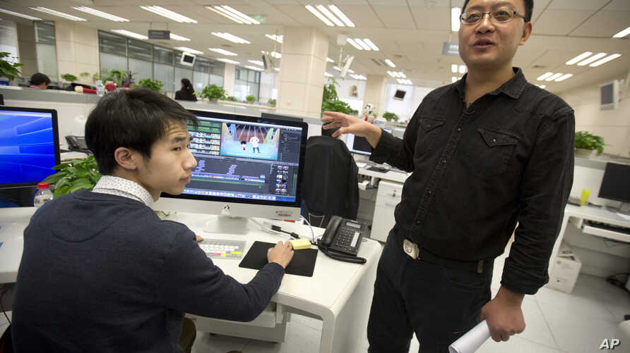 Xinhua All-Media Service deputy director Li Keyong reviews a video editor's animated political cartoon in the organization's updated offices in Beijing, Feb. 24, 2016.