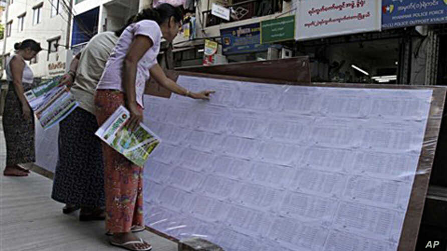 Women search their names in the list of eligible voters outside a local election commission office in downtown Rangoon, Burma, 21 Sept 2010
