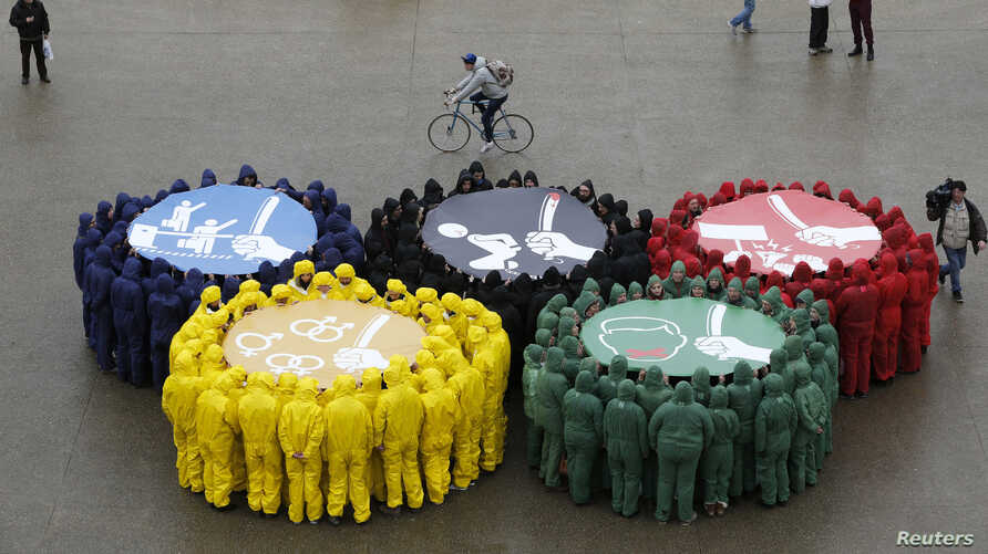 Olympic rings are displayed with images against restriction of speech and freedom of information, repression of demonstrations, discrimination due to sexual orientation and migrant's exploitation, as part of a protest by human rights organisations a