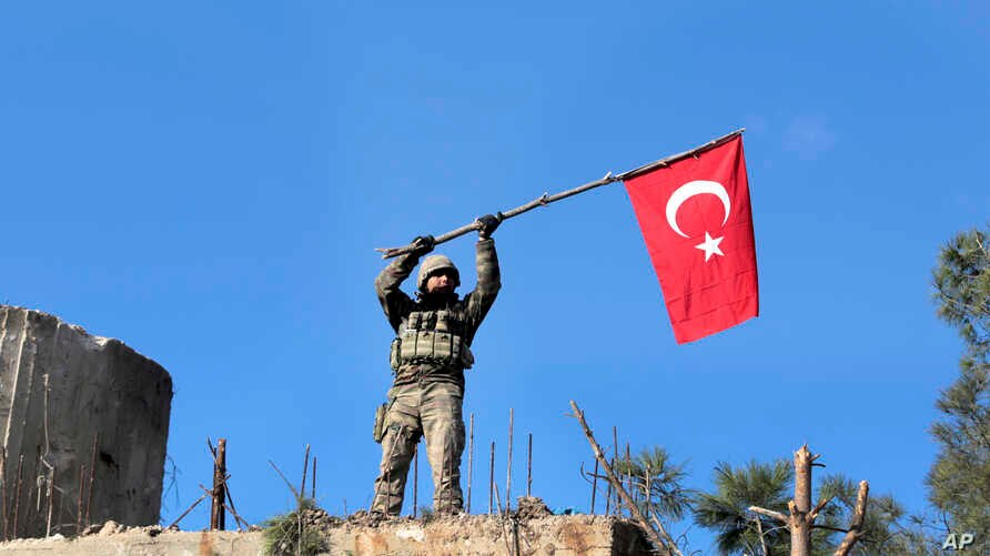 A soldier waves a Turkish flag as Turkish troops secure Bursayah hill, which separates the Kurdish-held enclave of Afrin from the Turkey-controlled town of Azaz, Syria, Jan. 28, 2018.