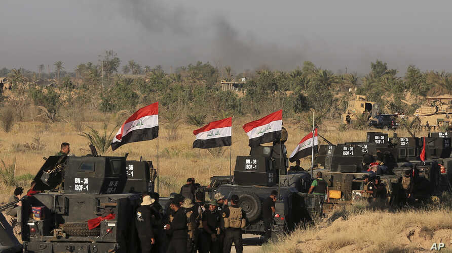 Smoke billows on the horizon as Iraqi military forces prepare for an offensive into Fallujah to retake the city from Islamic State militants in Iraq, May 30, 2016.