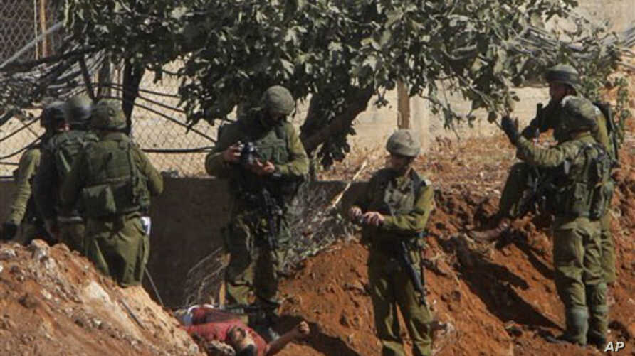 Israeli soldiers inspect the body of senior Hamas militant Nashad al-Karmi, in the West Bank city of Hebron, 08 Oct 2010