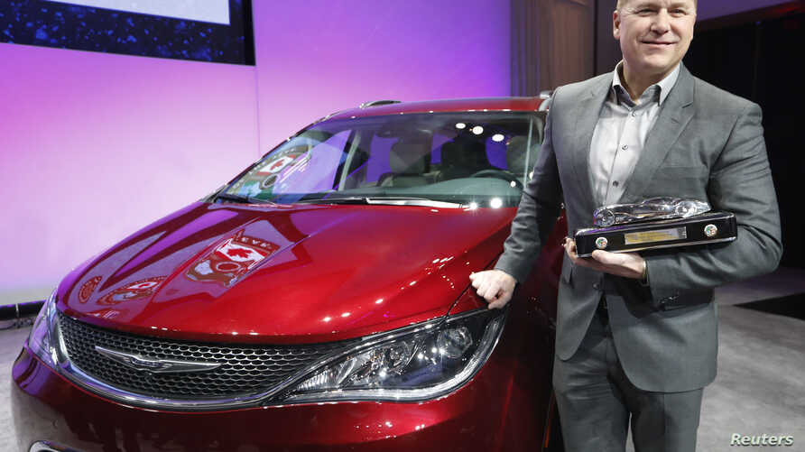 Tim Kuniskis, Head of Passenger Car Brands - Dodge, SRT, Chrysler and Fiat, FCA - North America, poses with the award for the Chrysler Pacifica as 2017 Utility Vehicle of the Year during the North American International Auto Show in Detroit, Michigan