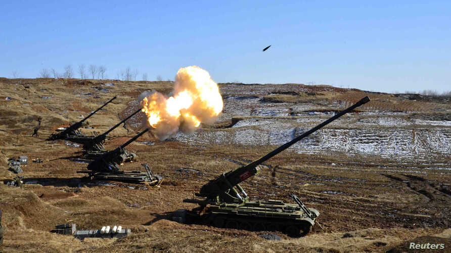 FILE - North Korea's artillery sub-units, whose mission is to strike Daeyeonpyeong island and Baengnyeong island of South Korea, conduct a live shell firing drill to examine war fighting capabilities in the western sector of the front line in this pi