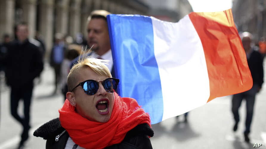 A far-right supporter marches next to French flag near the statue of Joan of Arc for his traditional march, May 1, 2017, in Paris.