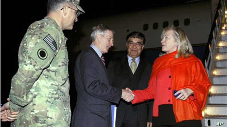U.S. Secretary of State Hillary Rodham Clinton shakes hands with U.S. Ambassador to Afghanistan Ryan Crocker as Afghan chief of protocol Hamid Saddiq (2nd R) and Lt. General Curtis Scaparotti (left) look on upon Clinton's arrival in Kabul, Afghanista