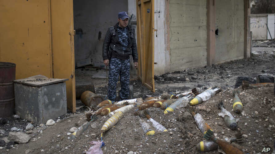 FILE - A member of the Federal Police stands next to unexploded bombs left by Islamic State group militants on the western side of Mosul, Iraq, March 22, 2017.