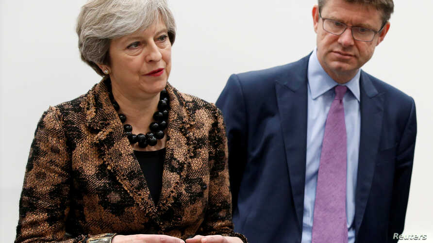 "FILE - Britain's Prime Minister Theresa May and Secretary of State for Business Greg Clark are pictured in the West Midlands, Nov. 20, 2017. Clark says British officials ""understand the anger of workers and shareholders when bosses' pay is out of ste"