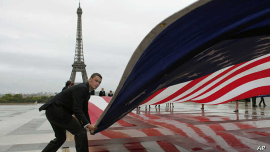 An American flag is unfurled in Paris during a commemoration to mark the 10th anniversary of the Sept. 11 attacks on the United States, at the Trocadero plaza , near the Eiffel tower, Sunday, Sept. 11, 2011.