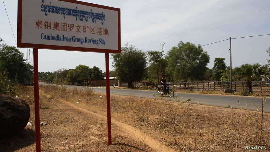 A man rides a motorcycle past a signboard for the Cambodia Iron Group at the Rovieng District in Preah Vihear province, February 10, 2013.