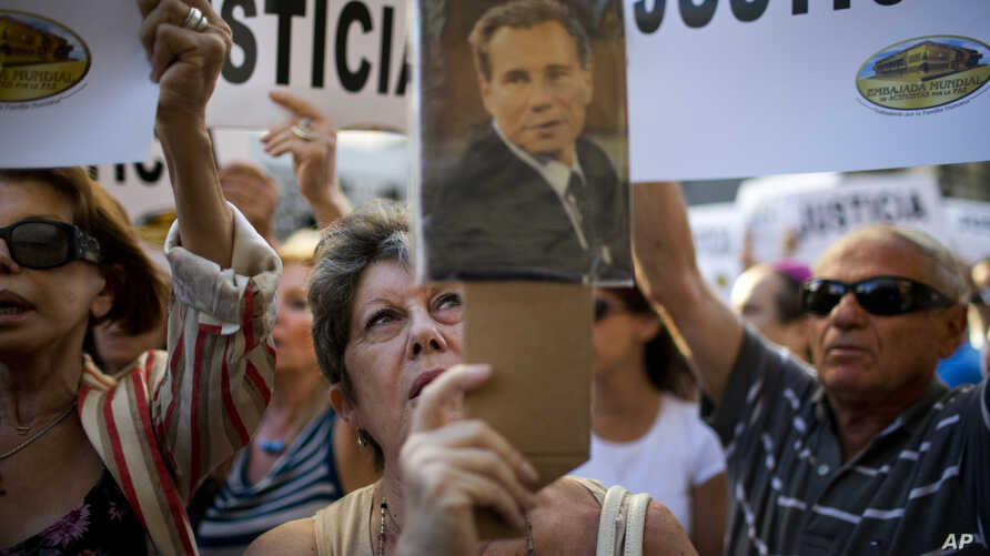 A woman sings the Argentine national anthem while holding a portrait of the late prosecutor Alberto Nisman outside the AMIA Jewish community center in Buenos Aires, Argentina, Jan. 21, 2015.