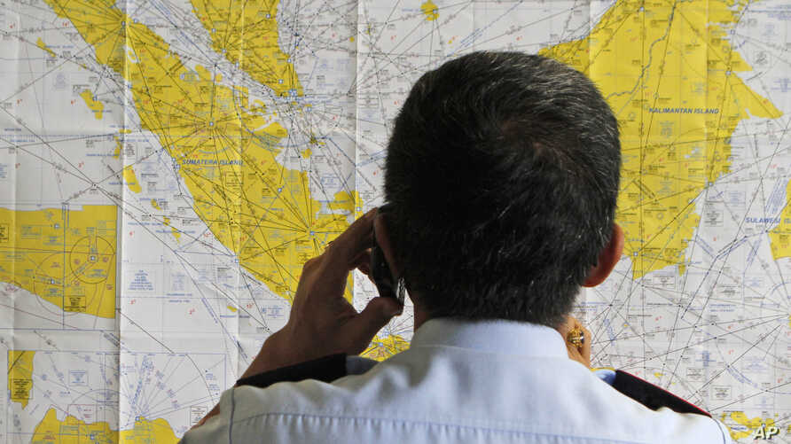 An airport official checks a map of Indonesia at the crisis center set up by local authority for the missing AirAsia flight QZ8501, at Juanda International Airport in Surabaya, East Java, Indonesia, Dec. 28, 2014.