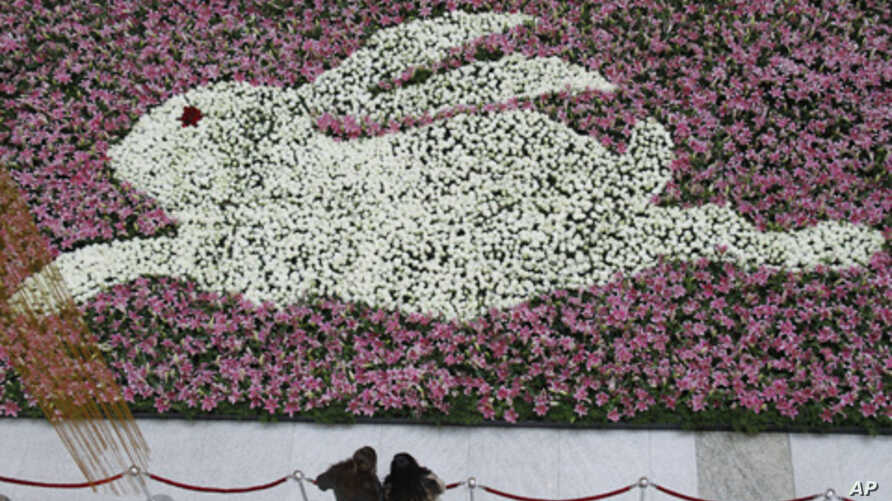 Customers look at a giant rabbit-shaped decoration made of white roses and lilies for the Chinese Spring Festival as part of Lunar New Year celebrations in Nanjing, Jiangsu province, China January 31, 2011.