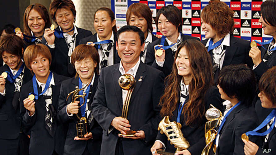 Japanese women's national soccer team coach Norio Sasaki, center, holding the World Cup trophy, poses with team players during a press conference in Tokyo, July 19, 2011.