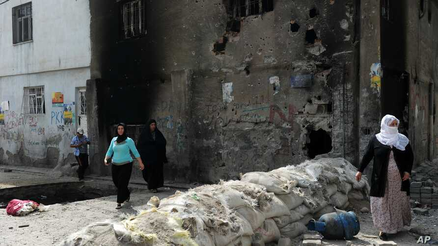 People emerge from their homes following the lifting of a curfew in the mainly Kurdish town of Cizre, Turkey, Sept. 12, 2015.