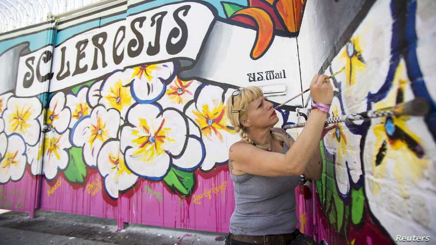Street artist Lydia Emily Archibald, who was diagnosed with Multiple Sclerosis in 2012, touches up her mural aimed at raising awareness about the disease in Los Angeles, April 9, 2015.