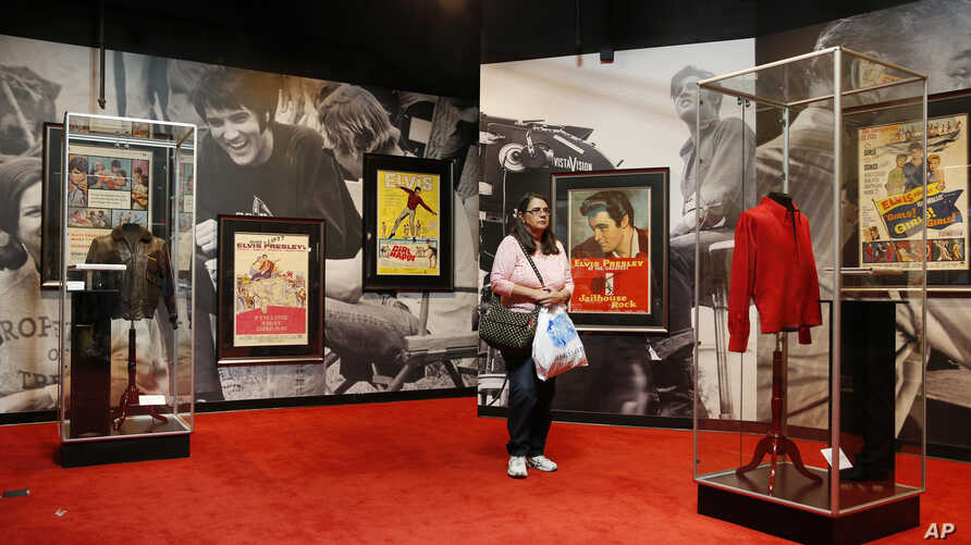 """A visitor scans items on display at """"Graceland Presents Elvis: The Exhibition"""" at the Westgate Las Vegas Resort and Casino, April 23, 2015."""
