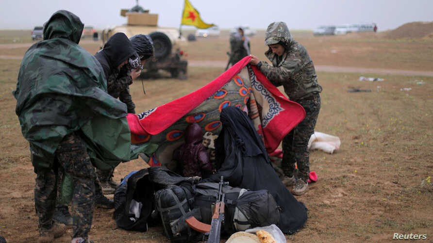 Members of the Syrian Democratic Forces help a woman near the village of Baghuz, in Deir el-Zour province, Syria, March 7, 2019.