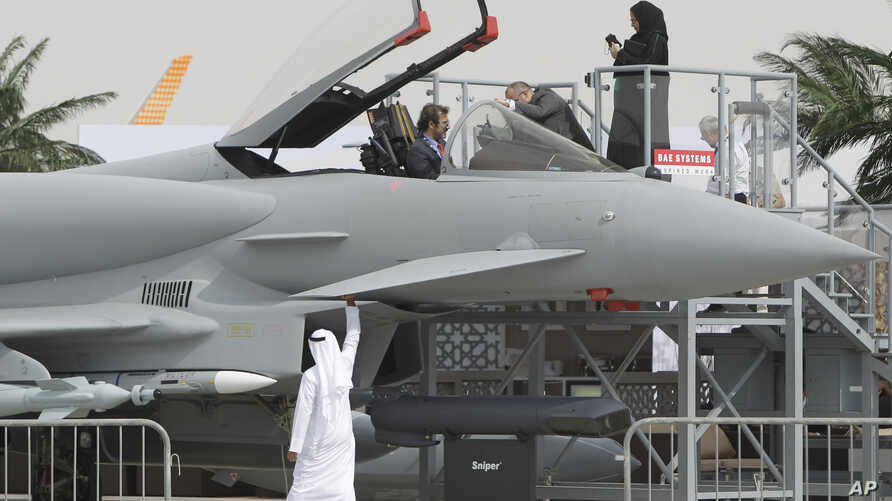 An Emirati woman, top right, and others view a replica of the Eurofighter Typhoon jet during the opening day of the Dubai Airshow in Dubai, United Arab Emirates, Nov. 17, 2013.