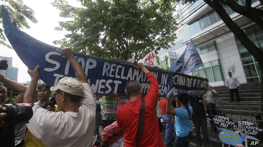 Demonstrators, carrying a boat, rally outside the Chinese Consulate at the financial district of Makati city, east of Manila, Philippines, to protest China's reclamations of disputed islands off South China Sea, July 3, 2015. The reclamations have st