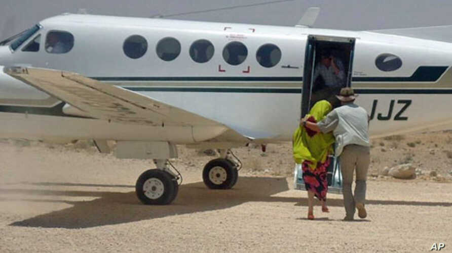 British hostage Judith Tebbutt (L) is escorted to a plane at Adado airport after she was released in central Somalia, March 21, 2012.