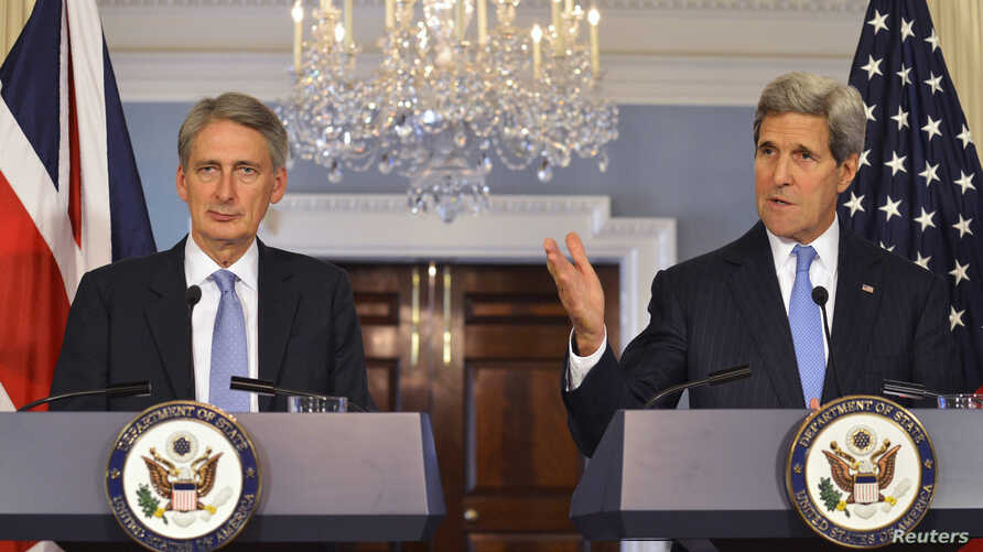 U.S. Secretary of State John Kerry (R) makes remarks as Britain's Foreign Secretary Philip Hammond looks on, during a press availability at the State Department in Washington Oct. 8, 2014.