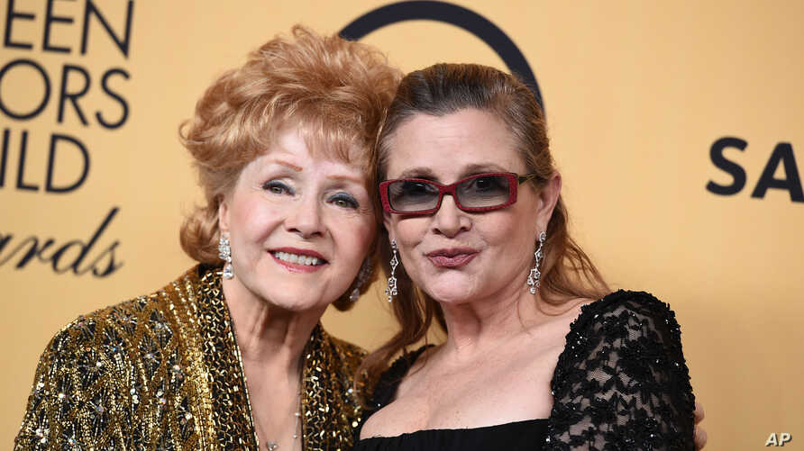 Debbie Reynolds, winner of the Screen Actors Guild lifetime award, left, and Carrie Fisher pose in the press room at the 21st annual Screen Actors Guild Awards at the Shrine Auditorium, Jan. 25, 2015, in Los Angeles.