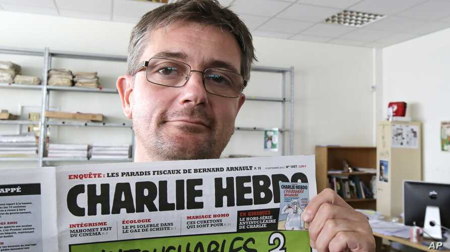 FILE - In this Sept.19, 2012 file photo, Stephane Charbonnier also known as Charb , the publishing director of the satyric weekly Charlie Hebdo, displays the front page of the newspaper as he poses for photographers in Paris.