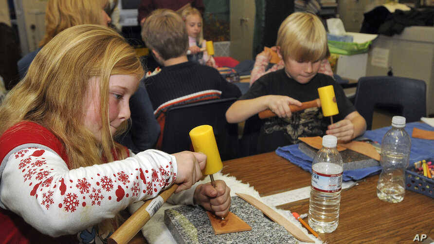 FILE - Idaho Arts Charter School students Maddison Thorpe, left, and Stefan Weiss work on their leather crafts as nationally known leather artist Deana  Attebery shows the students the different kinds of tools of the trade in Nampa, Idahao, Dec. 9, 2