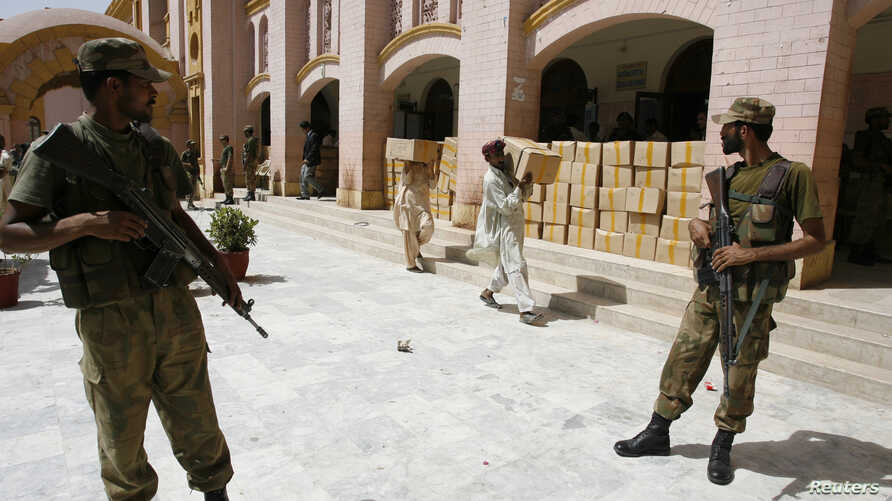 Pakistani Soldiers stand guard outside a district court as election commission workers carry election materials in Hyderabad May 8, 2013.
