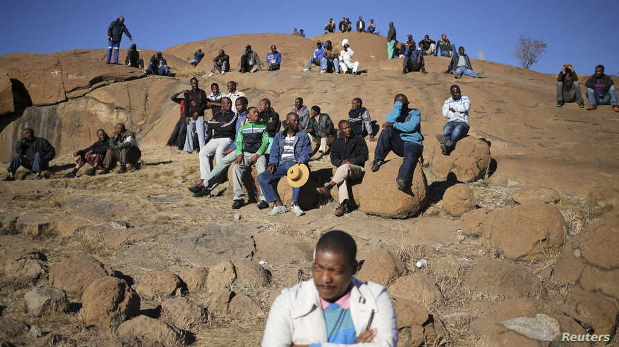 """Miners gather at a hill known as the """"Hill of Horror"""" ahead of the one-year anniversary commemorations to mark the killings of 34 striking platinum miners shot dead by police outside the Lonmin's Marikana platinum mine in Rustenburg, South Africa, Au"""