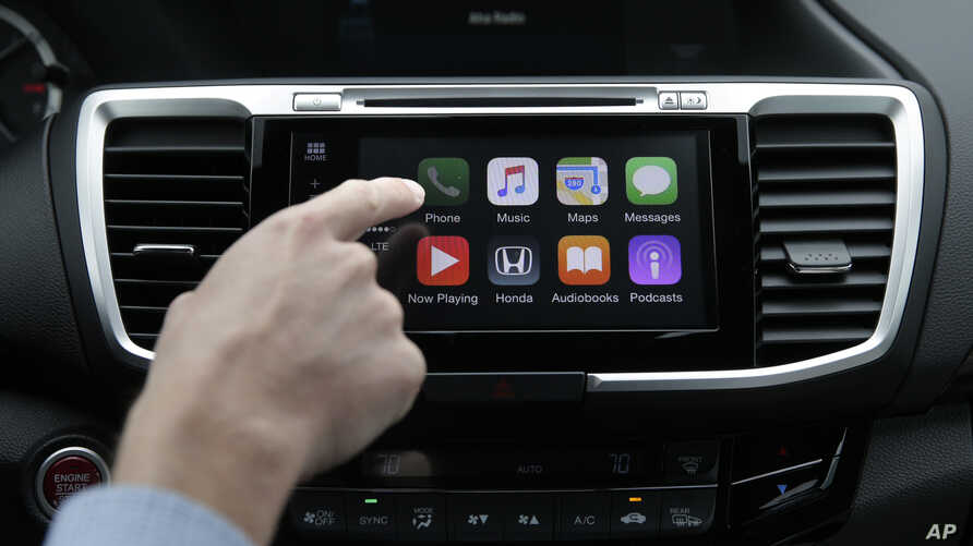 Chris Martin from Honda North America demonstrates Apple CarPlay, which lets drivers use an iPhone and its voice-activated assistant, Siri, to operate some of their vehicle's electronic controls and entertainment systems, in Torrance, Calif., August