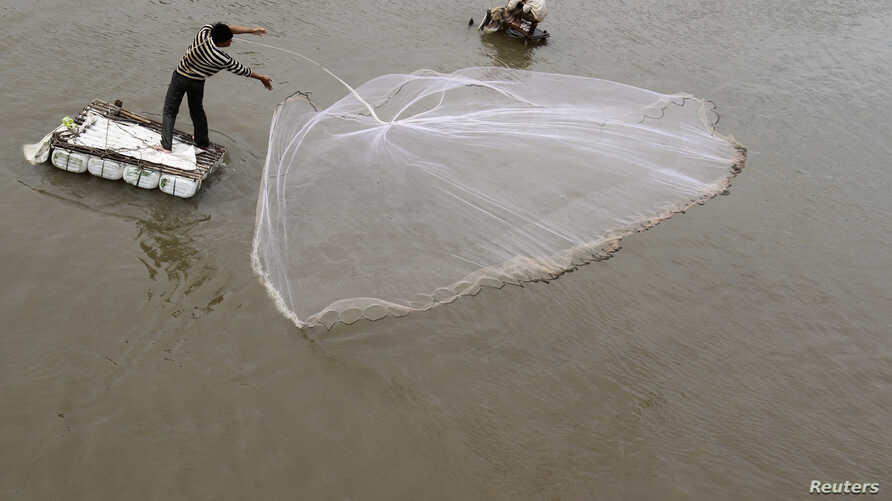 FILE - A man casts a fishing net on the Mekong riverbank in Phnom Penh, Cambodia.