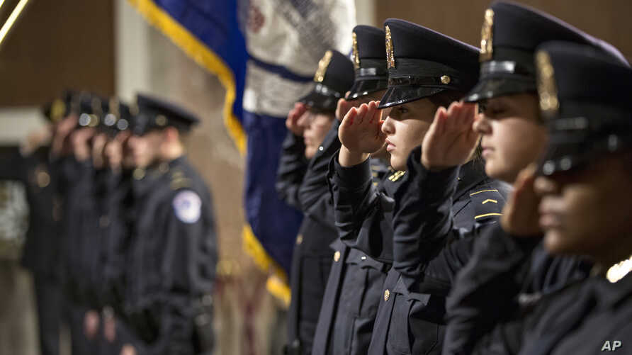 The newest members of the U.S. Capitol Police salute during their graduation ceremony on Capitol Hill in Washington, Nov. 20, 2015.