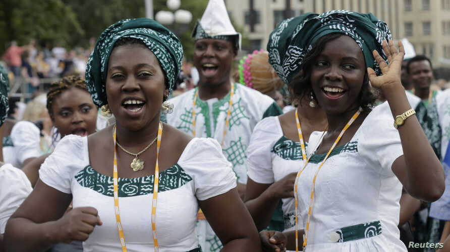"""Singers of """"Lagos City Chorale"""" choir of Nigeria greet people during the 2014 World Choir Games parade of nations in Riga, Latvia,  July 15, 2014."""