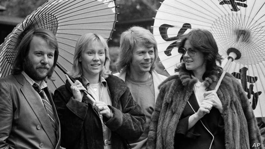FILE - Members of the Swedish pop group ABBA hold Japanese oil paper parasols in a light rain in the Japanese garden of their hotel in Tokyo, March 14, 1980. From left, they are Benny Andersson, Agnetha Faltskog, Bjorn Ulvaeus and Anni-Frid Lyngstad.