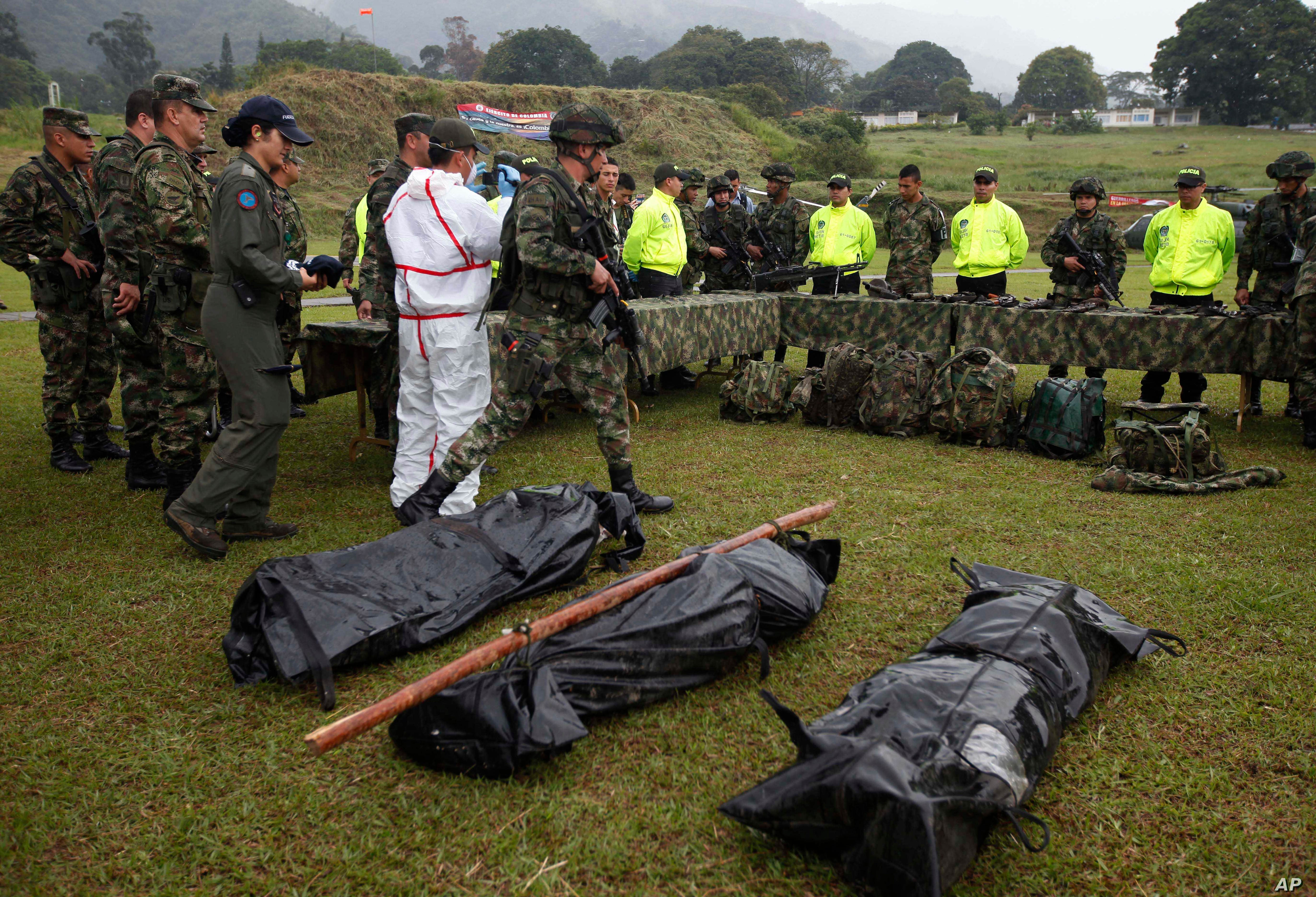 FILE - Bags containing the bodies of alleged rebels, and seized weapons, are shown to the press at military base in Ibague, Colombia, Jan. 22, 2014.