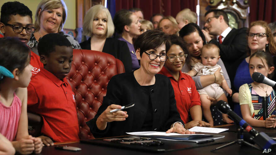 Iowa Gov. Kim Reynolds, center, signs a six-week abortion ban bill into law during a ceremony in her formal office in Des Moines, Iowa, May 4, 2018.