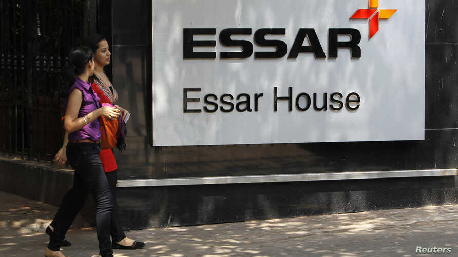 FILE - Employees walk past an Essar Group logo outside their headquarters in Mumbai May 20, 2013.