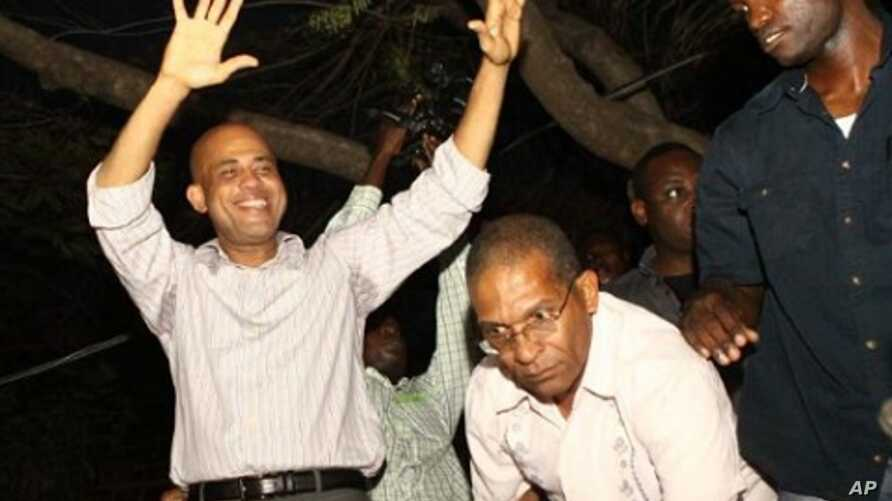 Haitian President-elect Michel Marthelly, left, reacts after the preliminary elections are announced, indicating he won the second round of the vote,  in Peggyvillle, Haiti April 4, 2011
