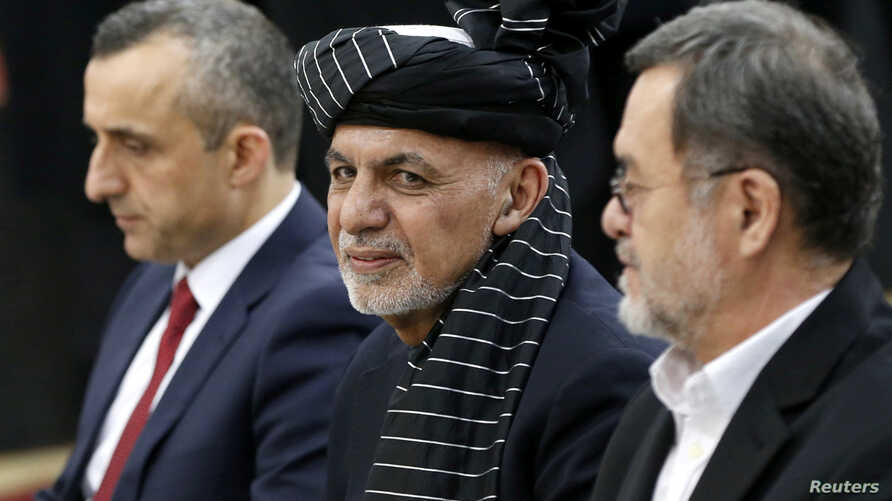 FILE - Afghanistan's President Ashraf Ghani, alongside his two vice president candidates, Amrullah Saleh, left, and Sarwar Danish, arrives to register as a candidate for the presidential election at Afghanistan's Independent Election Commission in Ka